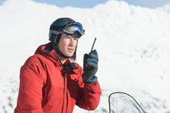 Snowmobiler talking on walkie-talkie