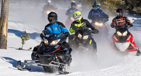 Snowmobilers riding along trail through wilderness